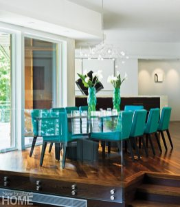 Ten turquoise chairs are a colorful foil to the glossy, black-stained bamboo table with blackened steel accents and legs.