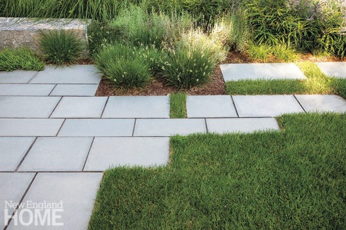The bluestone terrace has an asymmetrical edge that merges with a walk path. The grasses and ferns of the garden are intended to create a sense of movement.