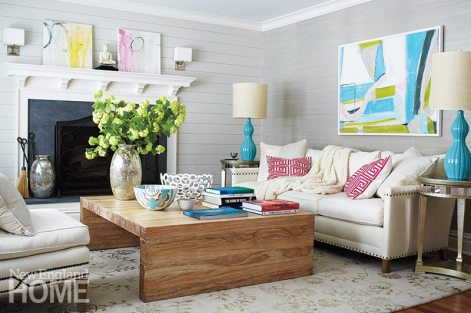 The horizontal paneling, gray grasscloth, pale upholstery, and vivid turquoise accessories give this home its beachy-casual feel.