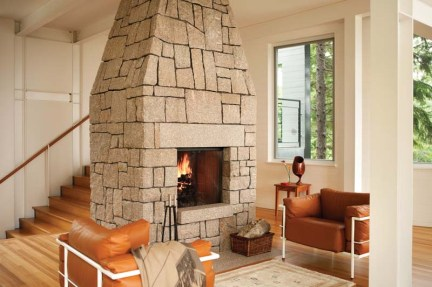 Local granite forms the massive fireplace; the freestanding chimney passes through the bedroom above.