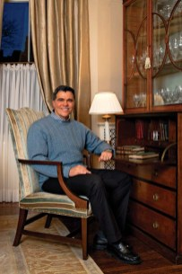 Designer Gerald Pomeroy perches on a living room armchair he reinvented with striped velvet.