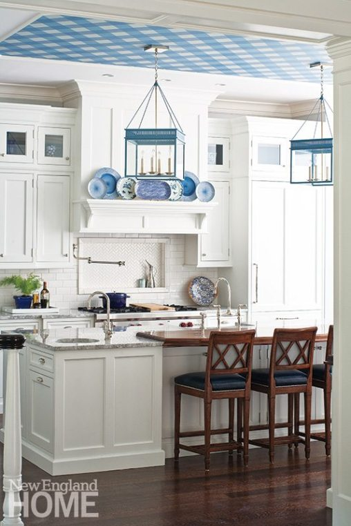 """The white-on-white kitchen is punctuated by a judicious use of blue: lanterns, decorative plates, and the room's """"little spark,"""" gingham-style wallpaper on the ceiling."""