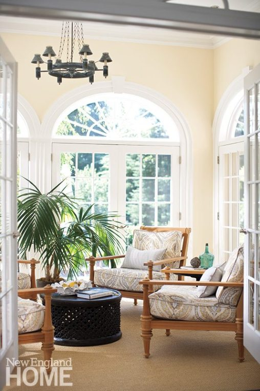 The sun-filled conservatory features half-round transom windows, a tropical feel, and furnishings that encourage kicking back.