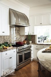 An opening above the granite kitchen counter offers a view to the living room and beyond.