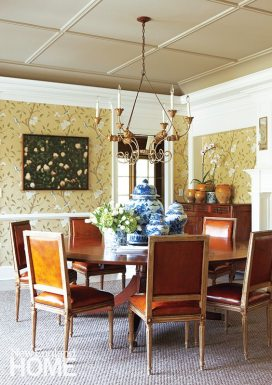Antique chairs surround a custom table that expands with pie-shaped leaves to seat the homeowners' extended family.