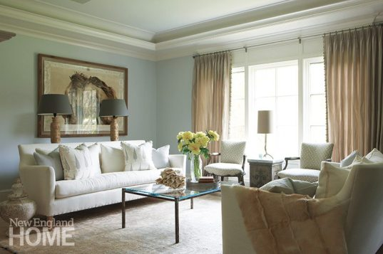 Pale gray walls lend the living room a calm feeling; an old iron gate topped with glass serves as a coffee table.