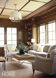 The hand-finished paneling of the library gleams against grasscloth-covered walls.
