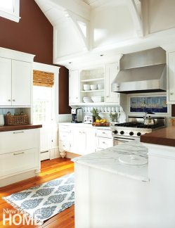 Rogers accentuated the ceiling beams in the kitchen by painting the walls chocolate brown.