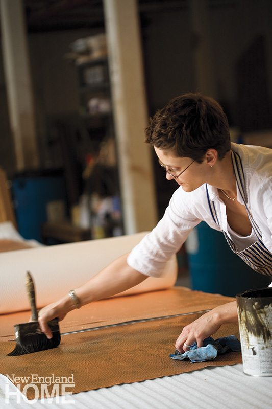 Artist Rebecca Thompson applies an antiquing agent to a copper-gilded wall covering.