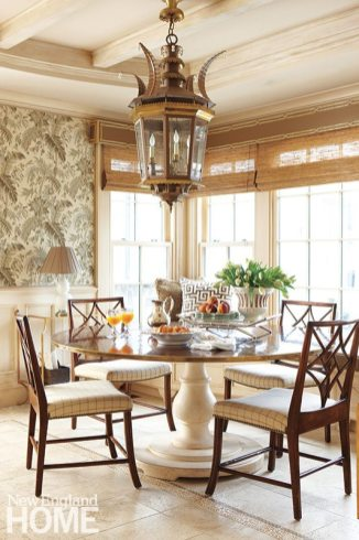 A breakfast area off the kitchen makes the first meal of the day special, with upholstered wall details and a massive lantern above a custom table.