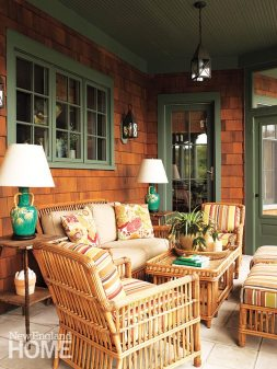 Chinoiserie lamps lend whimsy to a porch outfitted in rattan furniture dressed with practical Sunbrella-covered cushions.