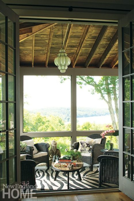 Vintage rattan furniture and a vintage surfboard table grace the screen porch.
