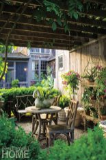 Faux bois furniture and a bevy of flowering plants turn the wisteria-draped pergola into a magical dining spot. Hand-forged exterior lighting is another handsome detail.