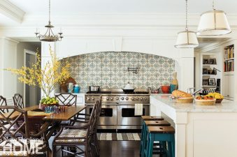 The refrigerator, pantry, and other utilitarian elements are stowed behind the kitchen's tiled wall.