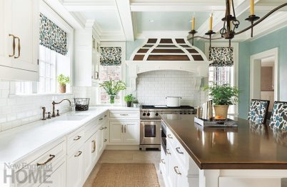 The out-of-date kitchen has been replaced with a bright and efficient space with a tiled back-splash, classic cabinetry, and limestone floor that fit right in with the home's traditional style.