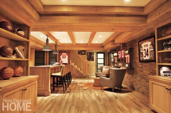 Restoration Hardware pendant lighting creates a casual ambience over the sports-bar portion of the basement, where brick veneer sets off an electronic scoreboard.