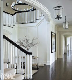 Defined by sleek interior architecture and a simple palette of black and white, the foyer sets a sophisticated tone.