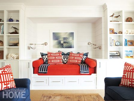 Bold orange and navy accents add zip to the white built-in shelves, cabinets, and queen-size daybed of the family room.
