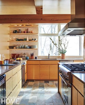 Plain drawers, absent of pulls, and open shelving holding a collection of pottery contribute to the modern air of the kitchen.