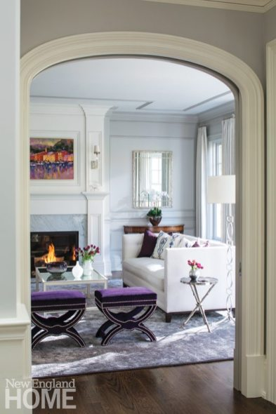 Pops of purple and a fiery painting brought back from Italy add a little kick to the living room's palette of soft grays.