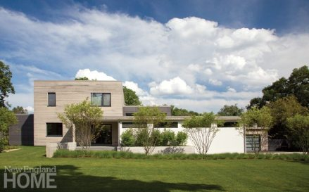 The street facade highlights the modern layers of the house, each clad in its own material.