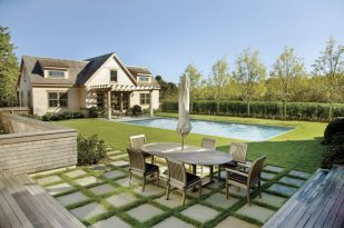 In the outdoor patio area, strips of green grass interweave between bluestone squares that match the pool coping.