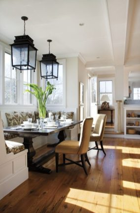 Oil-rubbed bronze antique lanterns hang over a trestle table in the casual dining area.
