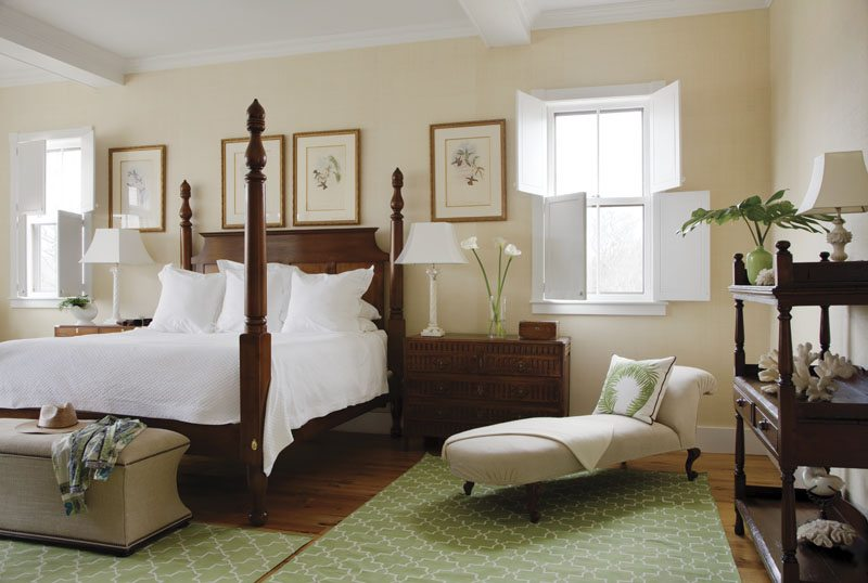A mahogany tall-post bed bedecked in white Sferra linens takes center stage in the downstairs master bedroom.