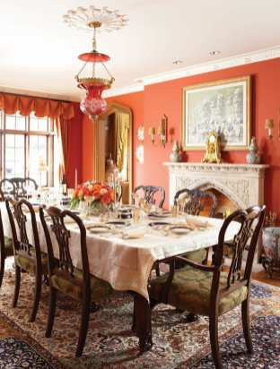 The formal dining room glows with persimmon-hued walls.