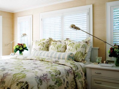 """""""Grasscloth walls give texture to a small room,"""" says Kathleen of the master bedroom, which fits a small custom chest of drawers on either side of the bed."""