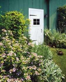 No ordinary utilitarian building, the green garage has its fair share of flowers including hydrangea, golden hops and Russian sage.