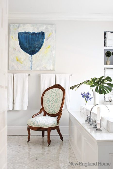 In the master bath, a family heirloom chair was recovered to fit the navy and turquoise theme.