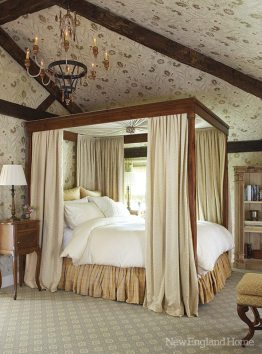 The bedroom, designed around the four-poster bed, gets a cozy European country house feel from the paper that covers the walls as well as the rustic beamed ceiling.