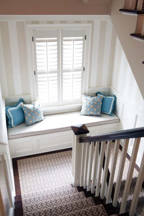 The wide-striped wallpaper from the foyer reappears on the stairway to the second floor.