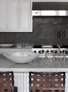 Smoke-gray Ann Sacks glass tile covers the kitchen backsplash while woven leather barstools from Mark Albrecht sit in the foreground.