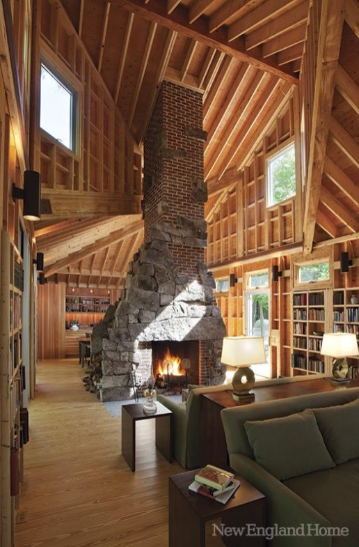 The rugged chimney rises to the multiple planes of the soaring ceiling.