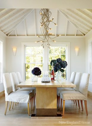 A soaring ceiling gives the dining room light and volume. The whimsical Italian chandelier is a wondrously modern choice to accompany the sleek oak table.