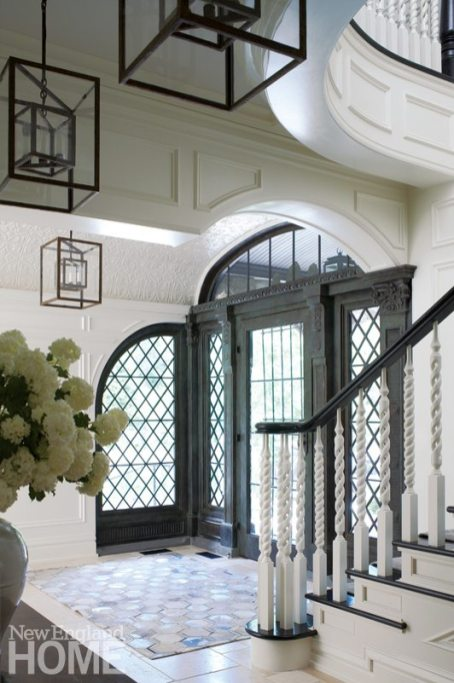 Large white entryway with leaded glass door.