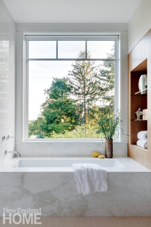 The master bath features a deep tub set in a deck of white marble with a view to the outdoors.