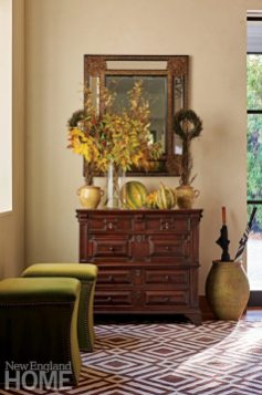 An antique chest and mirror provide a sense of permanence in the foyer and make the perfect platform for seasonal decor.