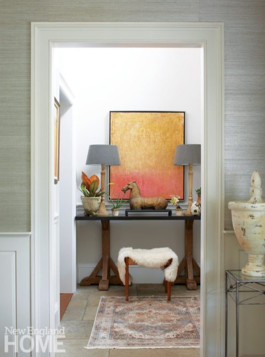 Orange and gray mingle again in the airy, double-height entry hall, where a painting by Stamford artist Arthur Vitello III and a zinc-topped console make a welcoming vignette.