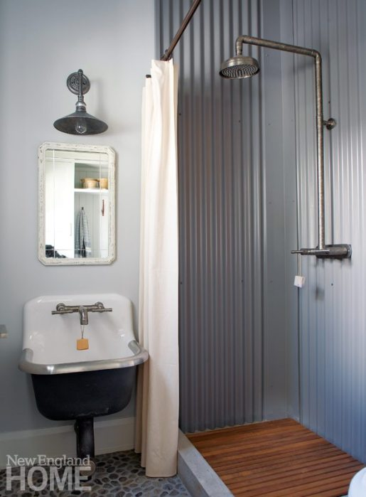 The same corrugated metal used on the outside of the house lines the shower in a bathroom near the mudroom; the shower fixture, too, is exterior-grade. The low, vintage-style sink from Kohler is well suited to utilitarian tasks.