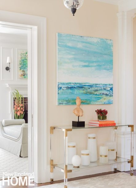 """A Lucite console table and contemporary art set the tone in the foyer, signaling, """"This is not an old house anymore,"""" says designer Elizabeth Benedict."""