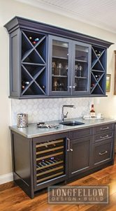 This custom wet-bar hutch includes a wine fridge. The wet-bar utilizes new materials and finishes such as a cold cast zinc countertop with a glass under-mount sink.