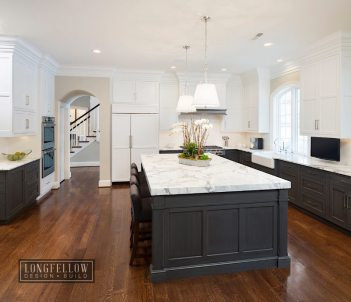 A traditional kitchen featuring cabinets with ebony stain on the bottom and crisp white paint on the uppers is both visually interesting and practical.