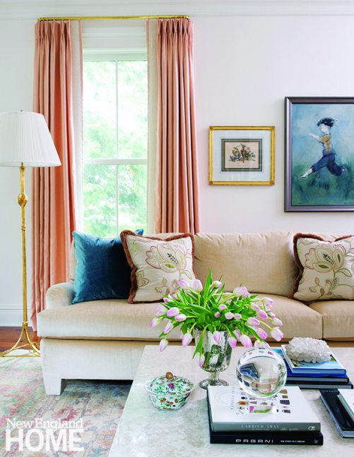 Designer Allison Caccoma's pretty palette for the living room includes wall paint of pink-tinged white and salmon-colored curtains.