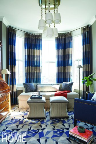 The den windows get their grandeur from horizontal-stripe drapes from Fabricut. Shades of blue take center stage in the space—which doubles beautifully as a guestroom—especially on the Samuel wing chair from Hickory chair. In another example of the perfect melding of styles, the antique secretary stands out against the modern Blackburn rug from Stark. The banquette sofa is by Antony Todd Home.