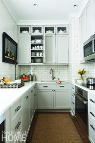 Simplicity reigns in the white-on-white galley kitchen with Bosch appliances, crackle finish subway tile, and custom cabinetry.