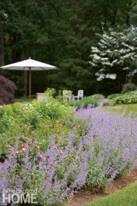A perennial garden leading to an outdoor seating area.
