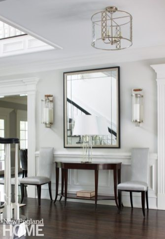 White entryway with polished nickel light fixtures